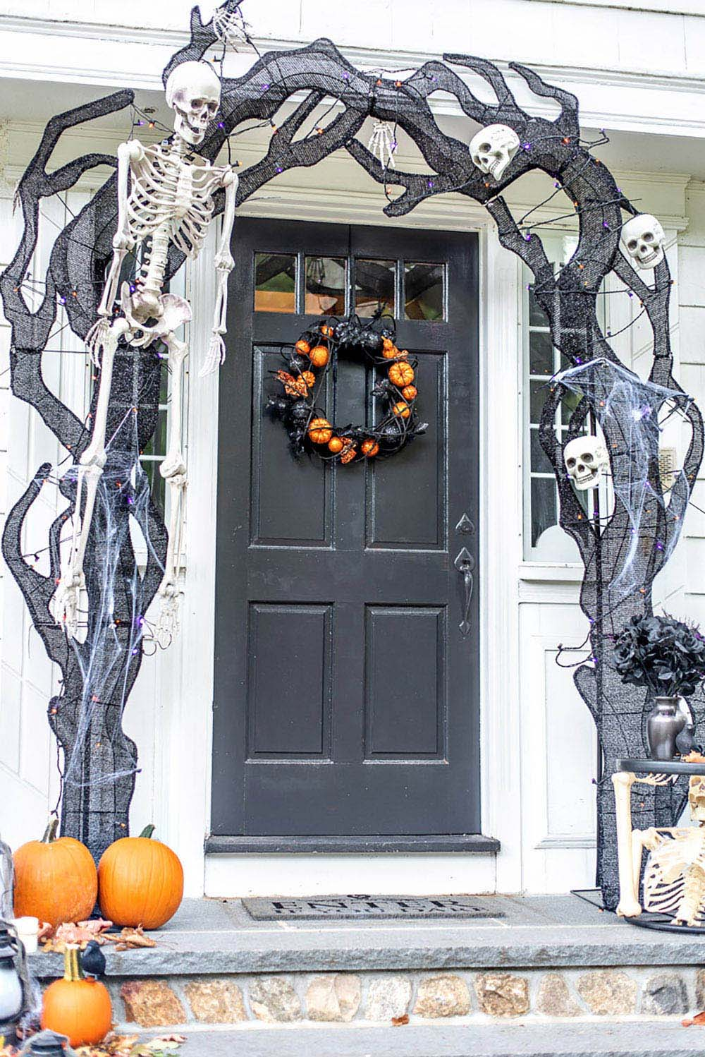 A close up shot of the front door with pumpkins, skeletons and faux smoke