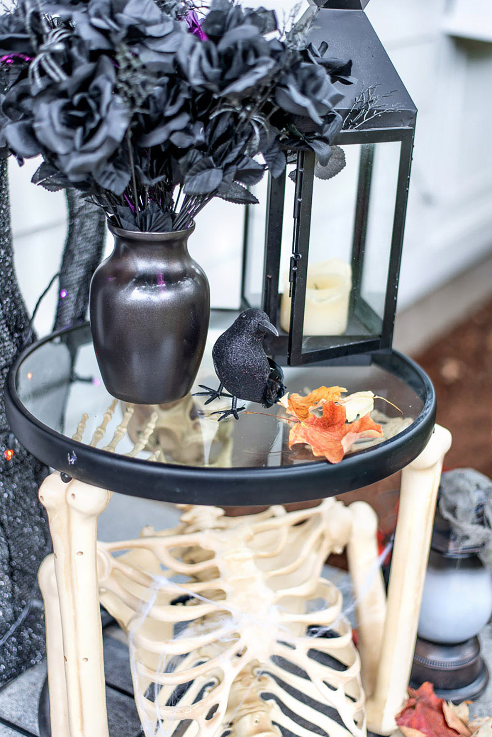 A skeleton side table with black roses and lantern on top