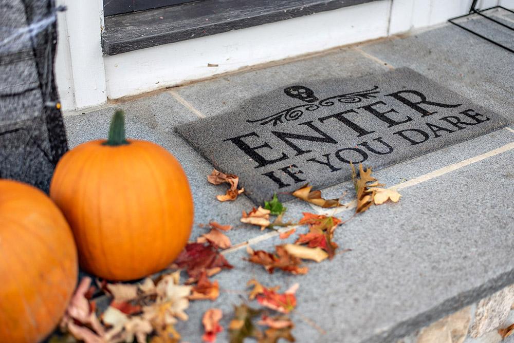 A close up shot of pumpkins and a door mat