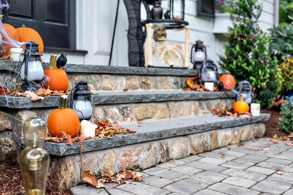 A close shot of lanterns and pumpkins on front steps