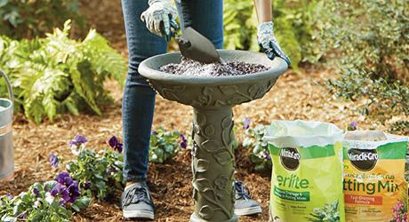 Gardener stirring perlite and potting mix in bird bath