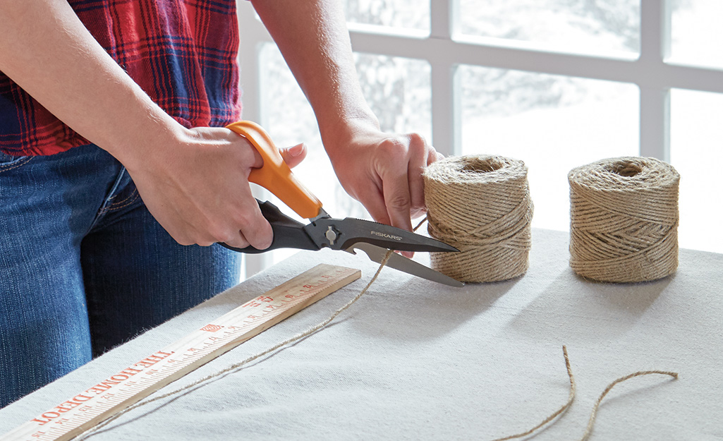 A person cutting a length of jute twine.