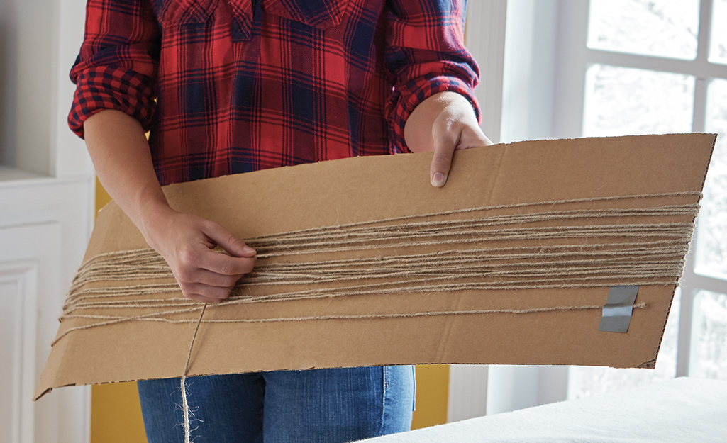 A person wrapping twine around a large piece of cardboard.