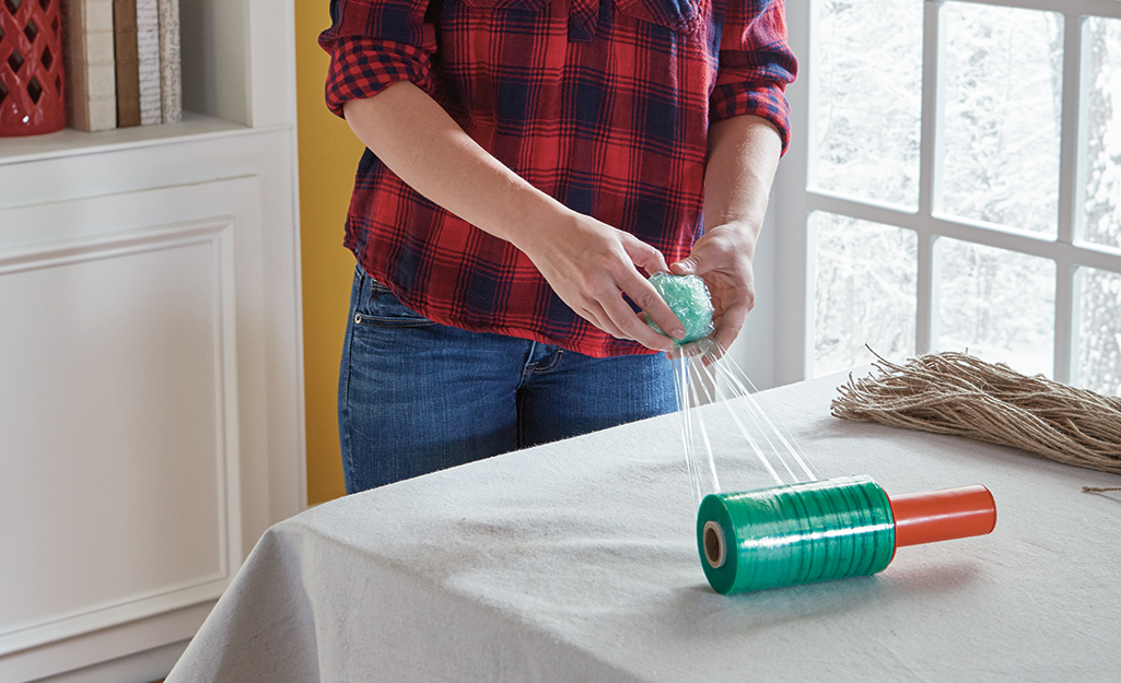 A person using plastic wrap to form a ball.