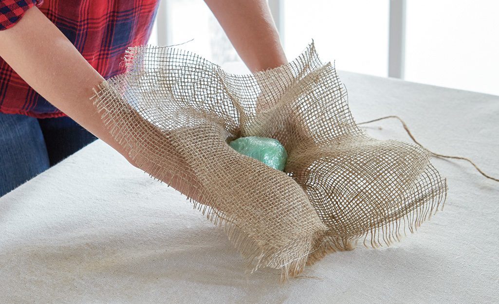 A person wrapping burlap around a plastic wrap ball.
