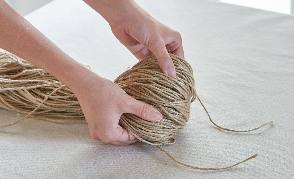 A person shaping a bundle of jute twine.