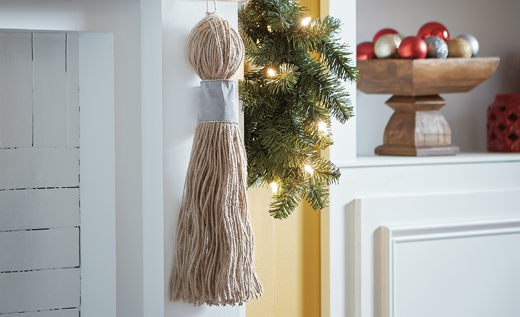 A twine DIY Christmas tassel hanging from a fireplace mantel.