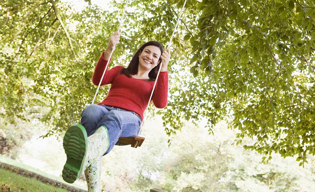 Một người lớn đu trên cây đu để kiểm tra xem nó có an toàn không.