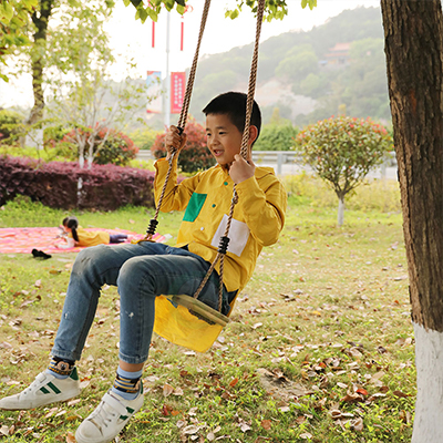 A young boy wearing a yellow shirt and jeans swinging in a tree swing.