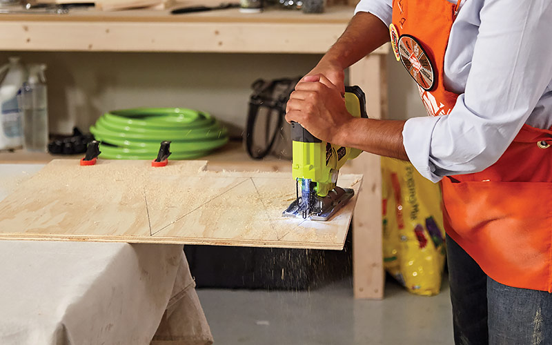 Man using a jigsaw to cut triangle shapes in plywood.