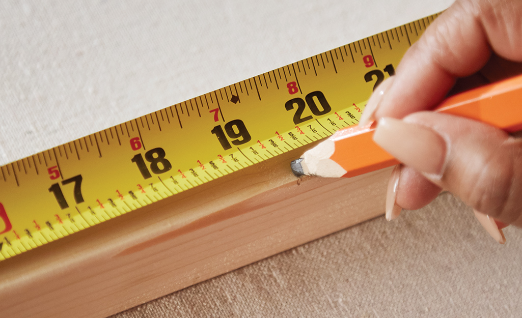Someone measuring wood and marking it.
