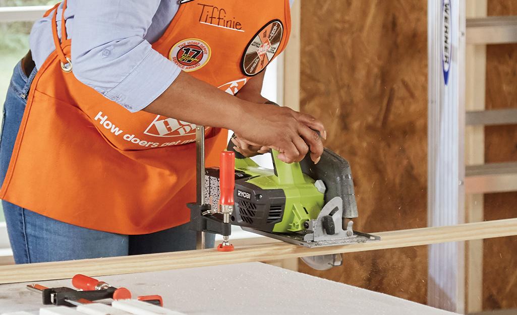 Home Depot associate cutting into lumber.