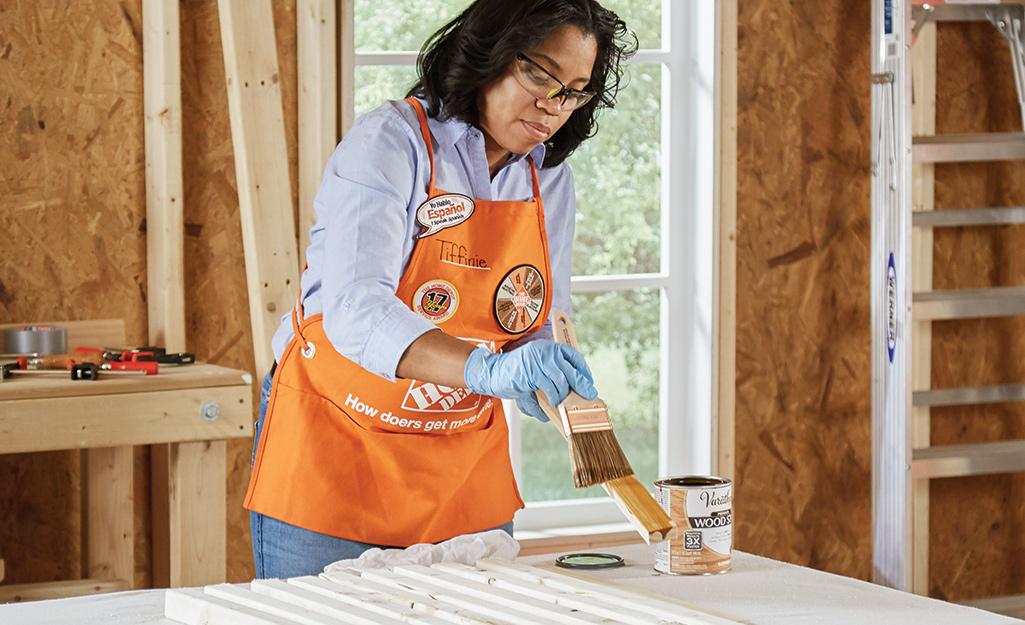 Home Depot associate staining wood.