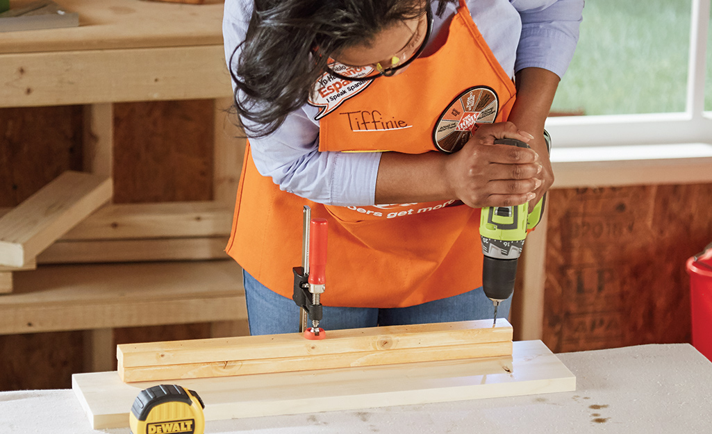 Home Depot associate drilling into the lumber.