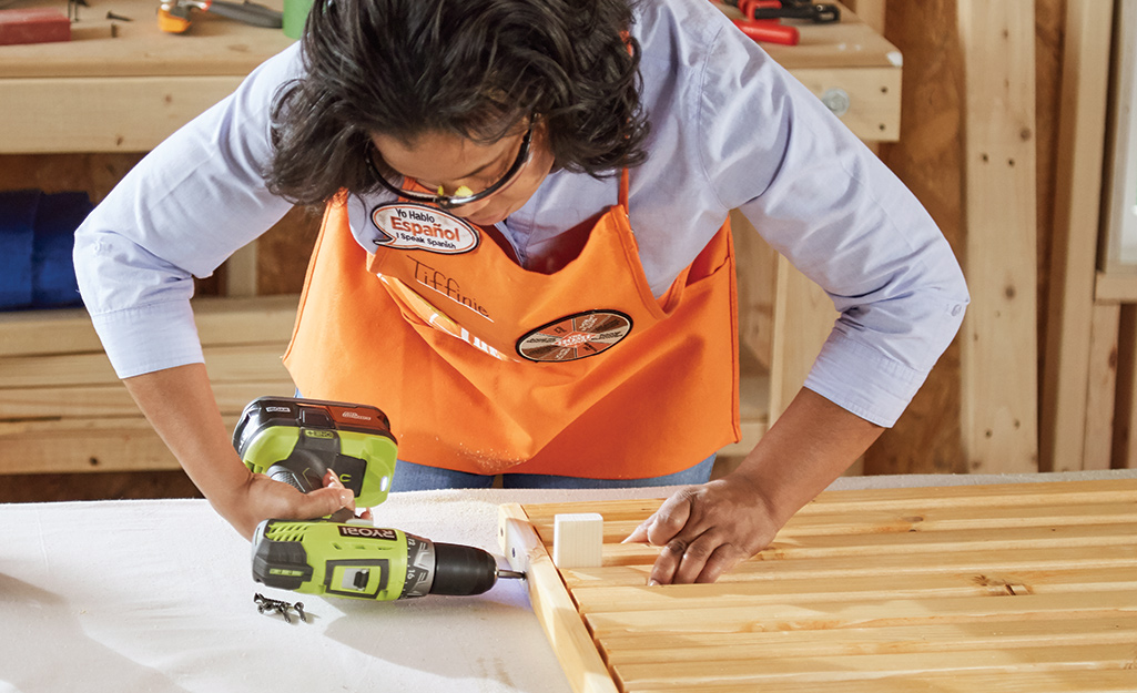 Home Depot associate drilling the slats together.
