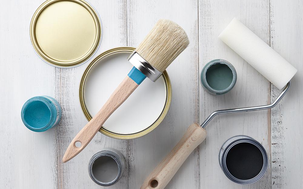 Nhiều loại hộp sơn, chổi quét và con lăn sơn trên bề mặt gỗ.