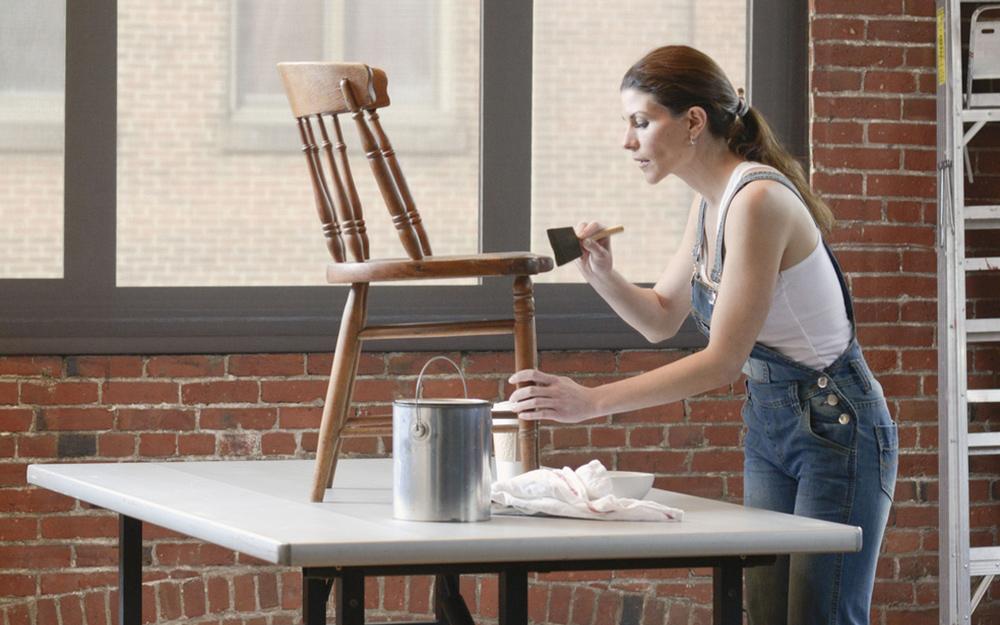 Một người phụ nữ vẽ một chiếc ghế.