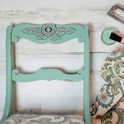 A mint green chair with paint supplies next to it.