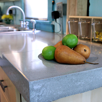 Fruit sits on a gray concrete countertop in a kitchen.