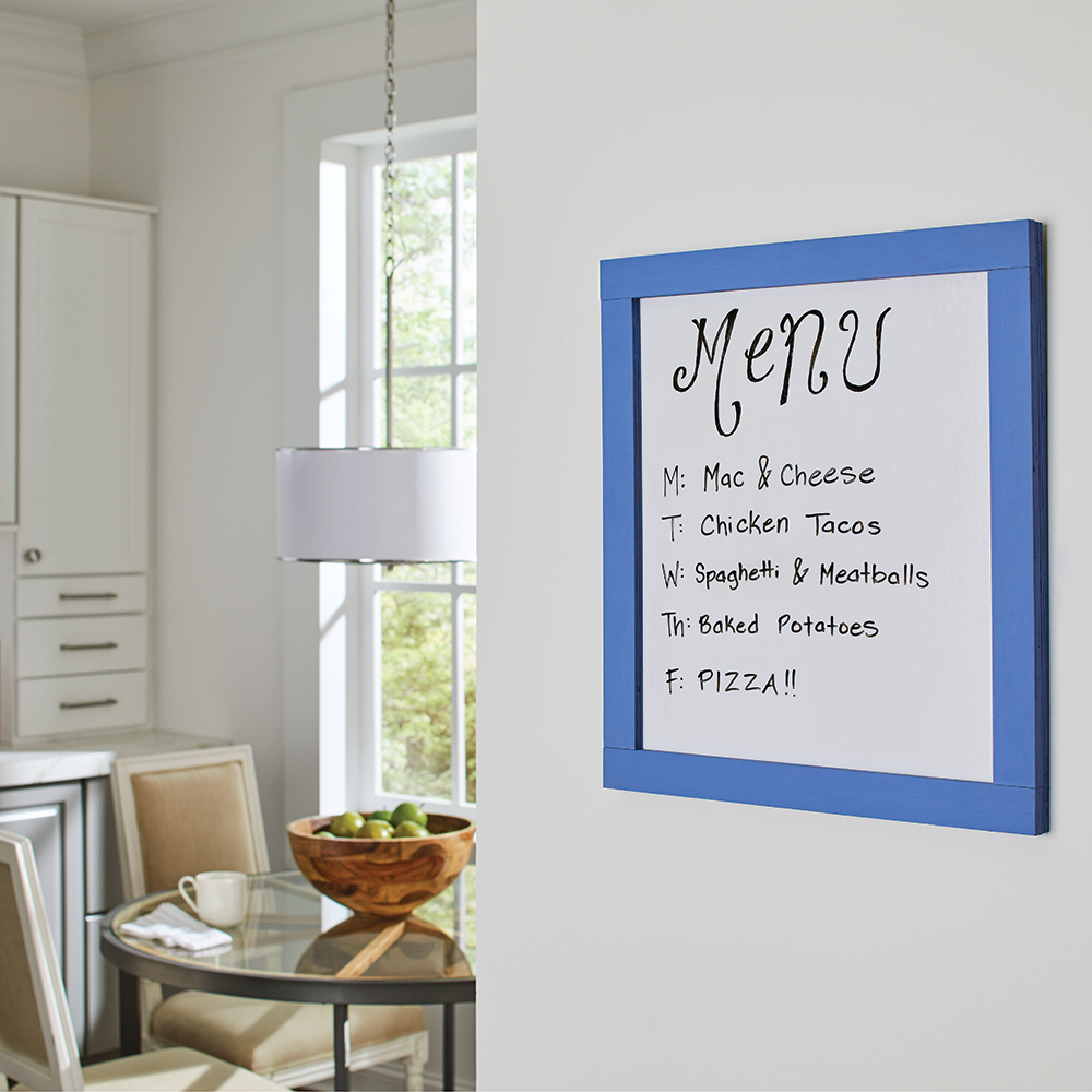 A dry erase menu board hangs in a sunny kitchen.