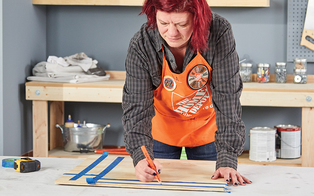 A woman measuring materials to create a dry erase menu board.