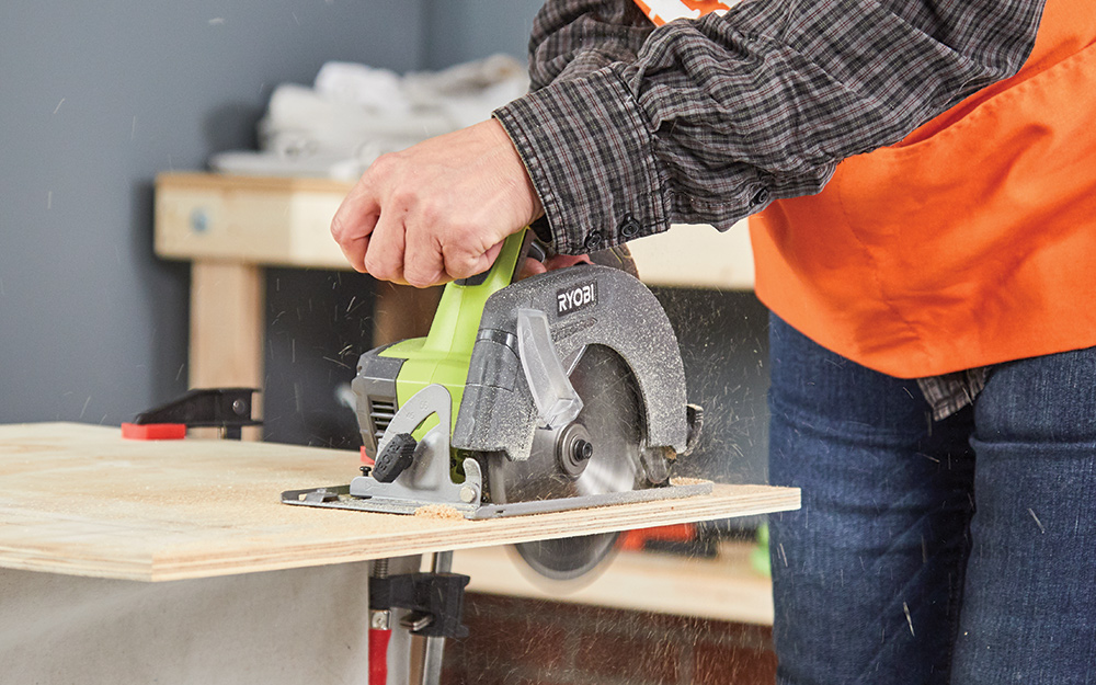 A person cutting plywood with a circular saw.