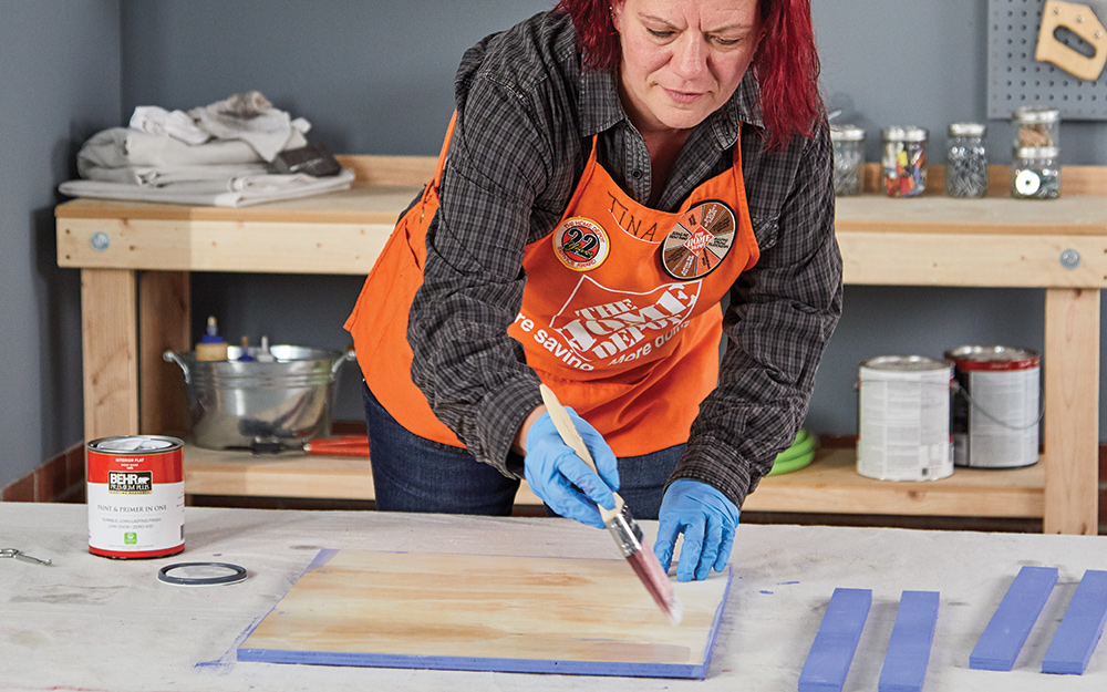 A woman staining boards to create a dry erase menu board.