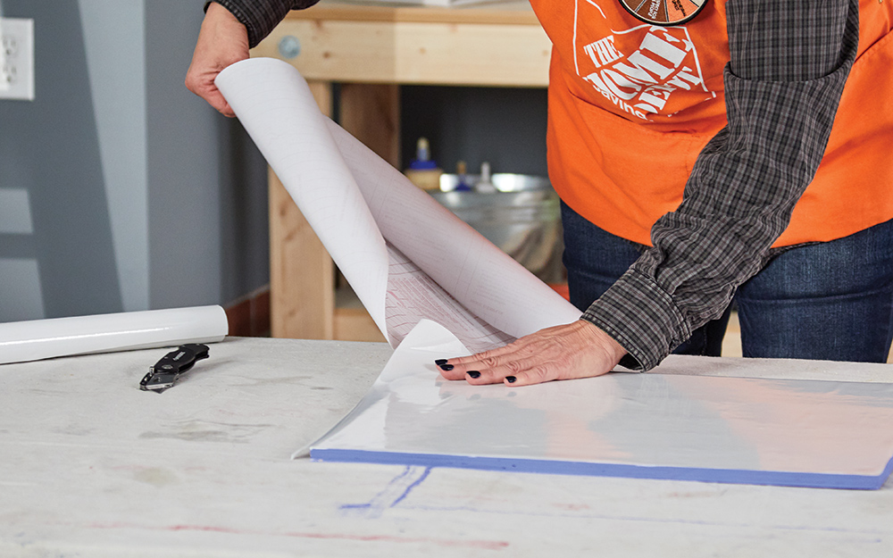 A woman applying contact paper to create a dry erase menu board.