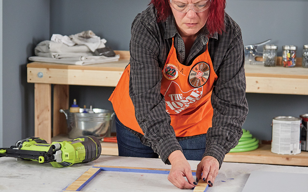 A woman creating a frame for a dry erase menu board.