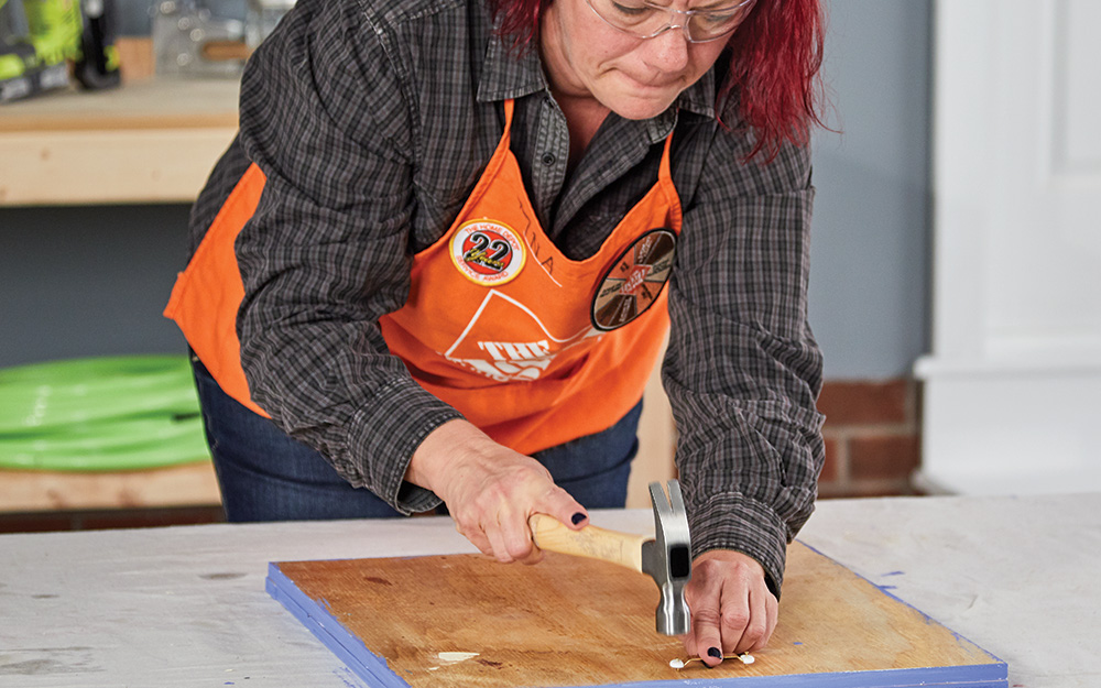 A woman attaching a hanger to a dry erase menu board.