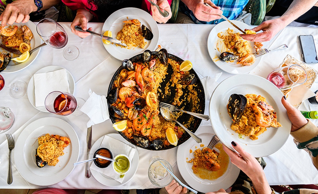 A group of people eating paella at a long table.
