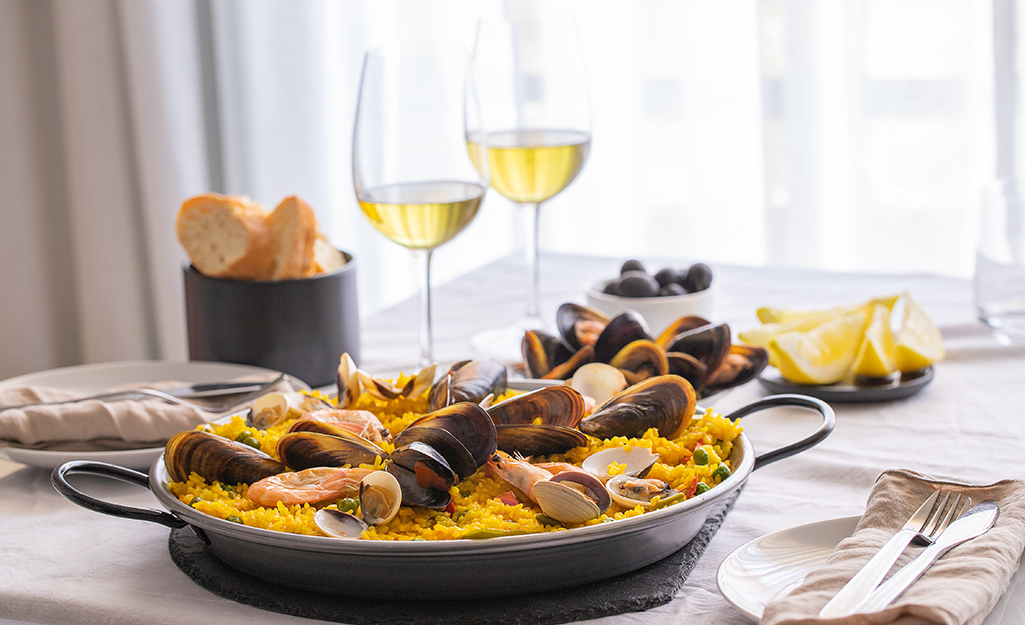 A finished paella dish on a table with bread and white wine.