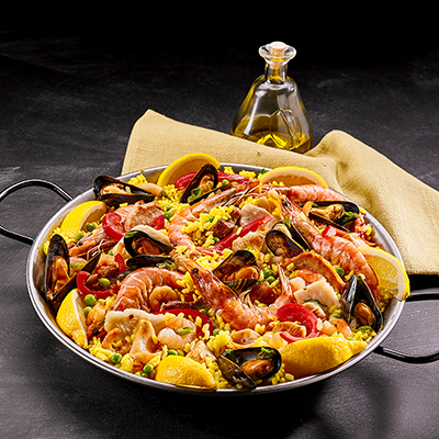 A dish of paella with seafood, sausage and chicken.