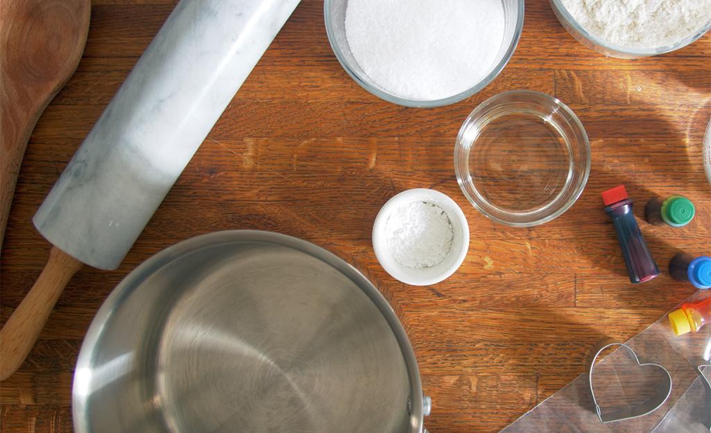 Ghim lăn, chảo sốt, màu thực phẩm và các nguồn cung cấp bột nặn khác trên quầy.