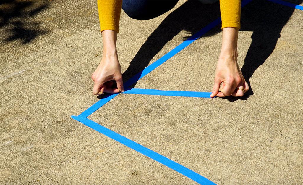 Một phụ nữ sử dụng băng của họa sĩ để phác thảo thiết kế của mình.
