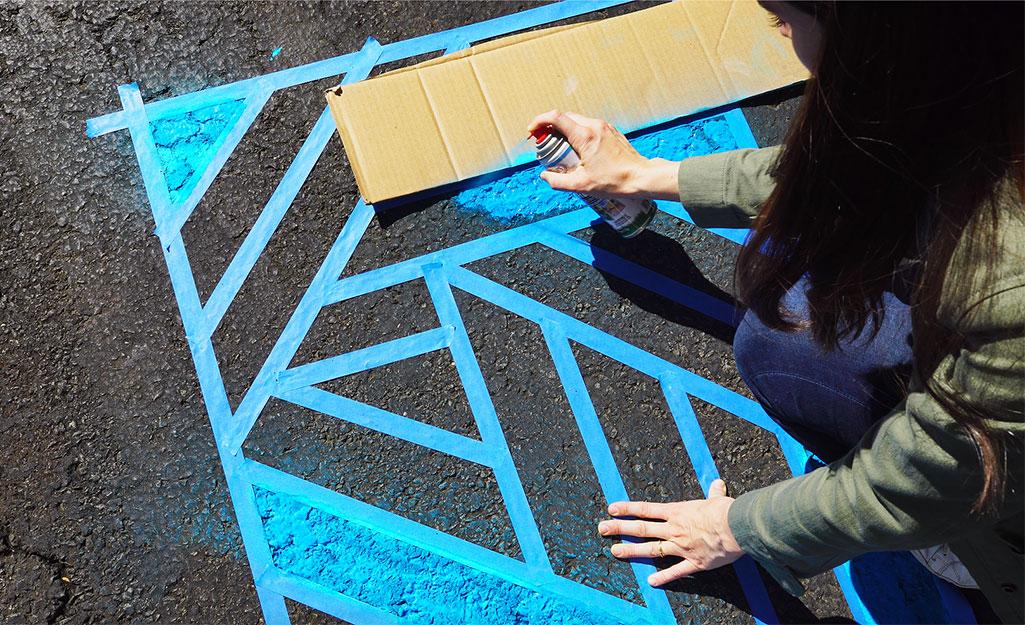Một người phụ nữ sử dụng một miếng bìa cứng để giữ màu sắc riêng biệt trong thiết kế.