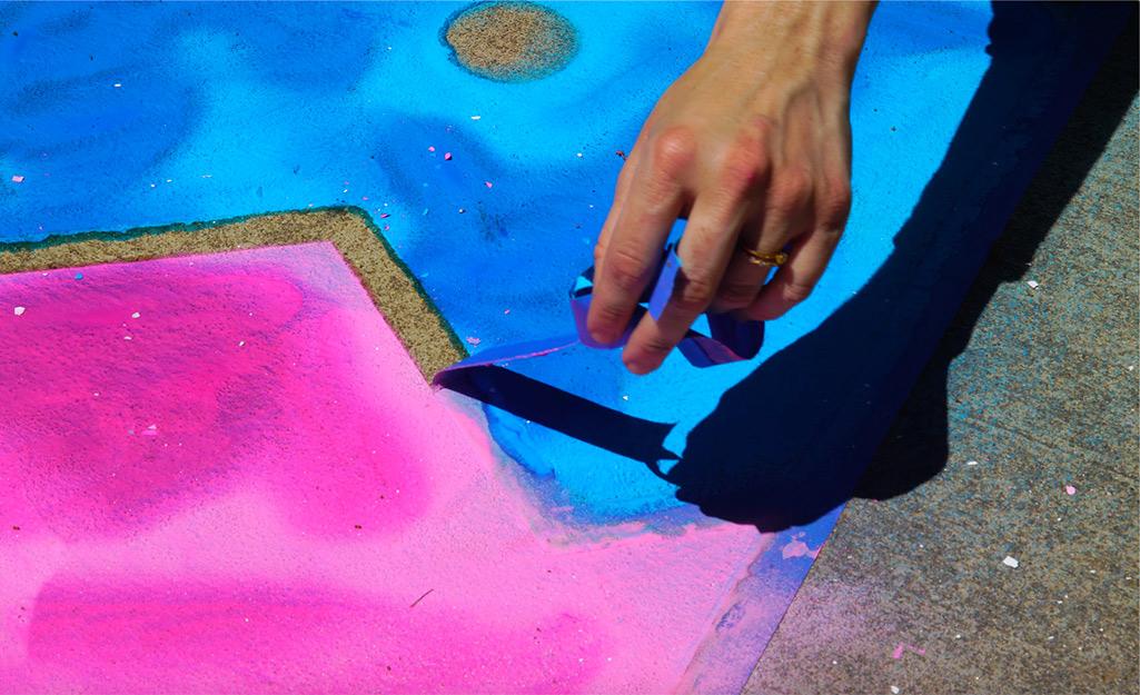 Một người phụ nữ gỡ băng của họa sĩ khỏi bức tranh phấn vỉa hè của mình.