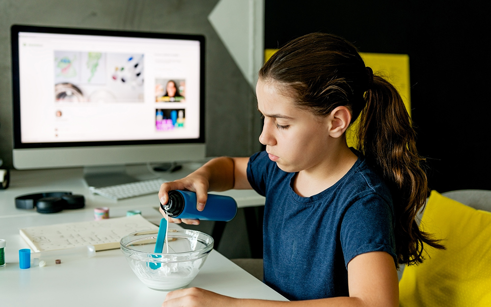 A girl adds slime ingredients to a bowl