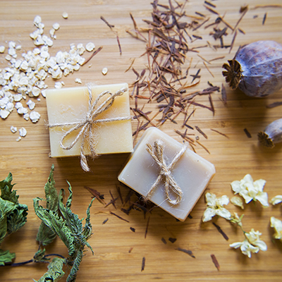 Homemade soap on a table with dried botanicals.