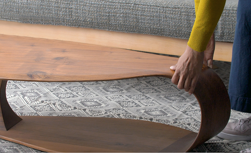 Ai đó đang di chuyển chiếc bàn cà phê bằng gỗ ấm áp trước chiếc ghế sofa màu xám