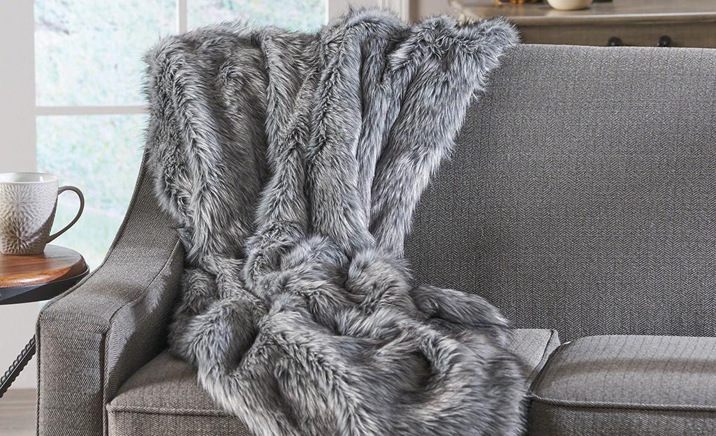 Ném lông thú giả màu xám và bạc nằm trên đi văng