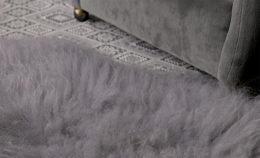 Tấm thảm lông giả rắn đặt trên tấm thảm màu xám in