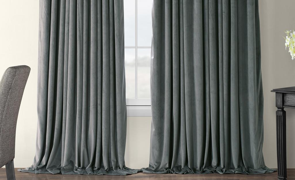 Màn dày màu xám treo trên cửa sổ đôi
