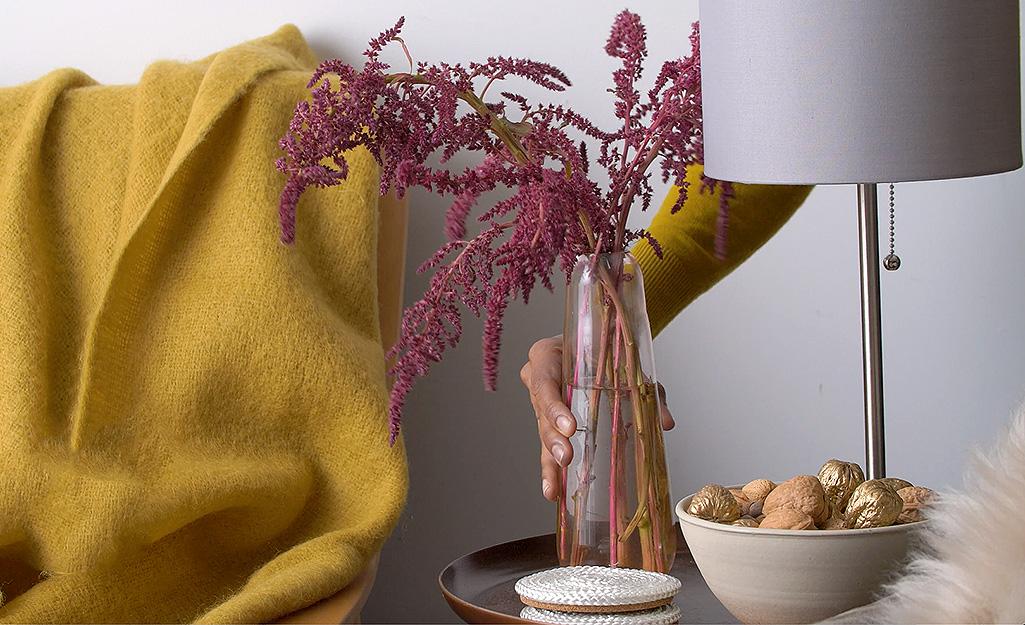 Một chiếc bình thủy tinh đầy hoa màu tím ngồi trên bàn cuối
