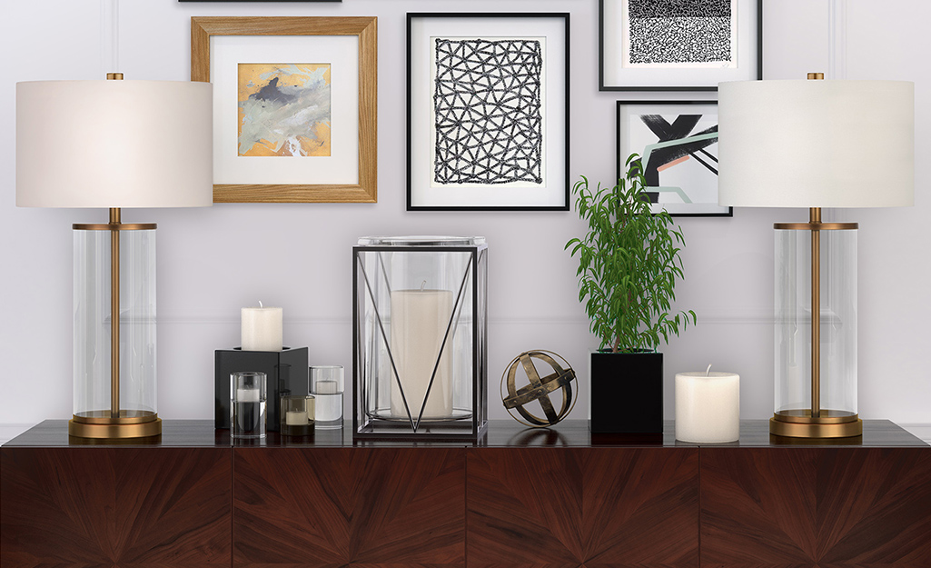 Hai chiếc đèn bàn bằng thủy tinh và đồng thau trên nền gỗ sẫm màu