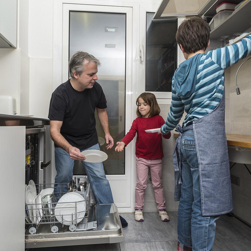 Family loading dishwasher together.