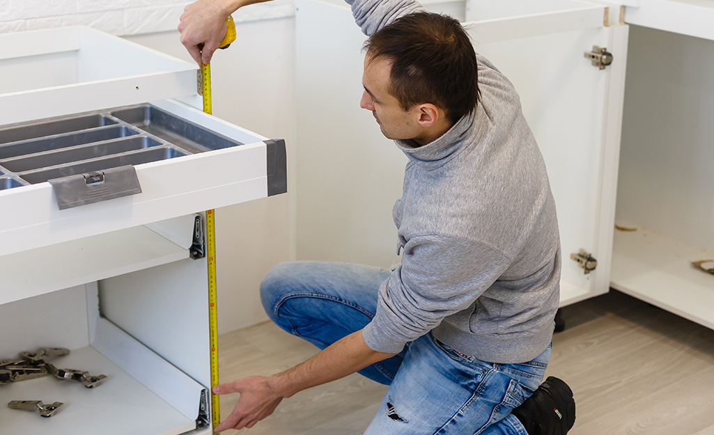 Man measuring the height of a cabinet space.