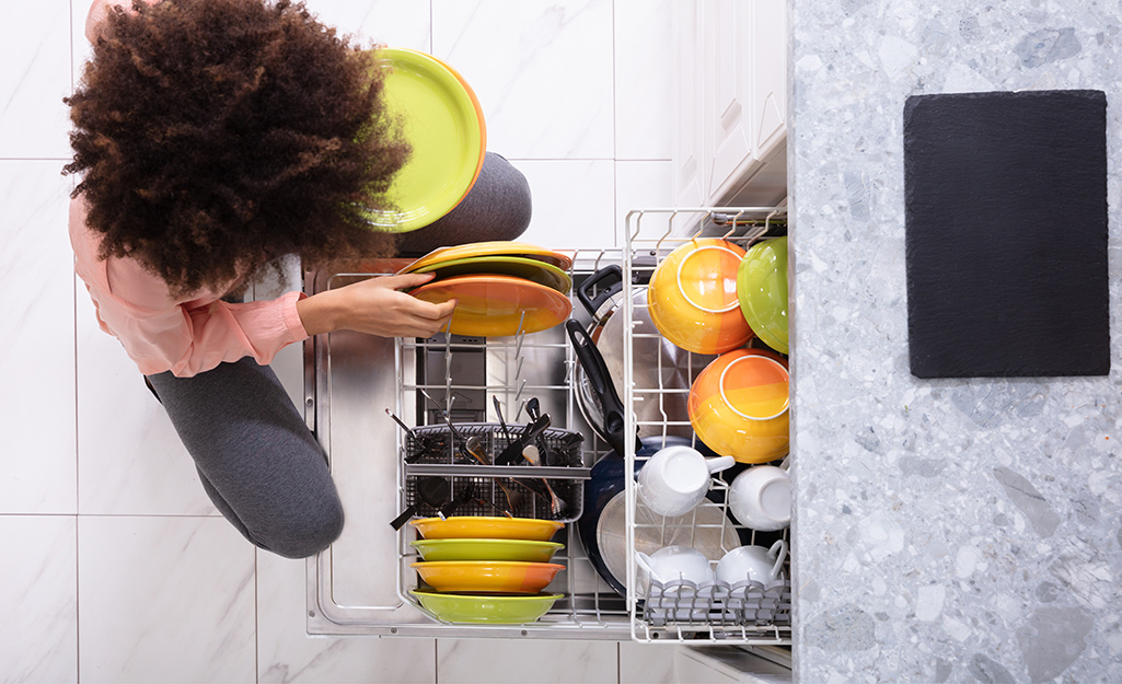 Someone pulling out dishes from a dishwasher.
