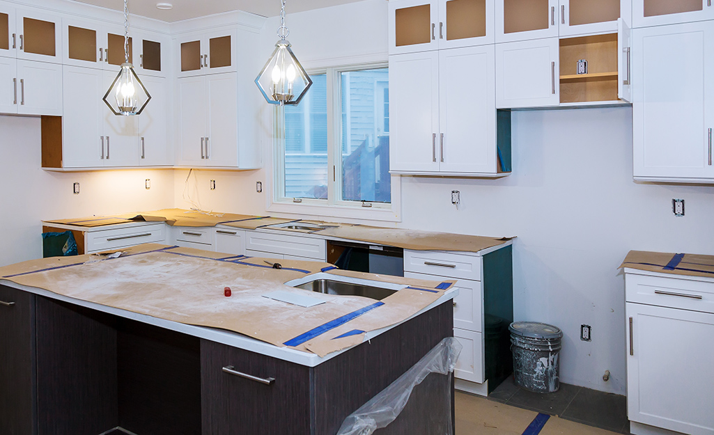 A kitchen with partially-installed cabinets and a large space where a refrigerator will be installed.
