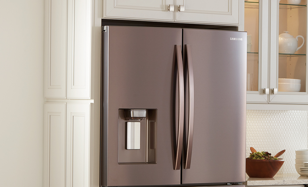 A built-in refrigerator with a couple inches of ventilation space between it and the upper cabinets.